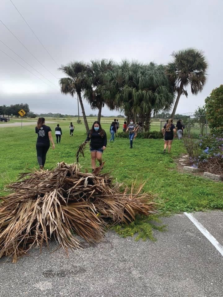 LHS National Honor Society Students voluntarily clean up palm fronds and other yard debris at Caloosa Humane Society.