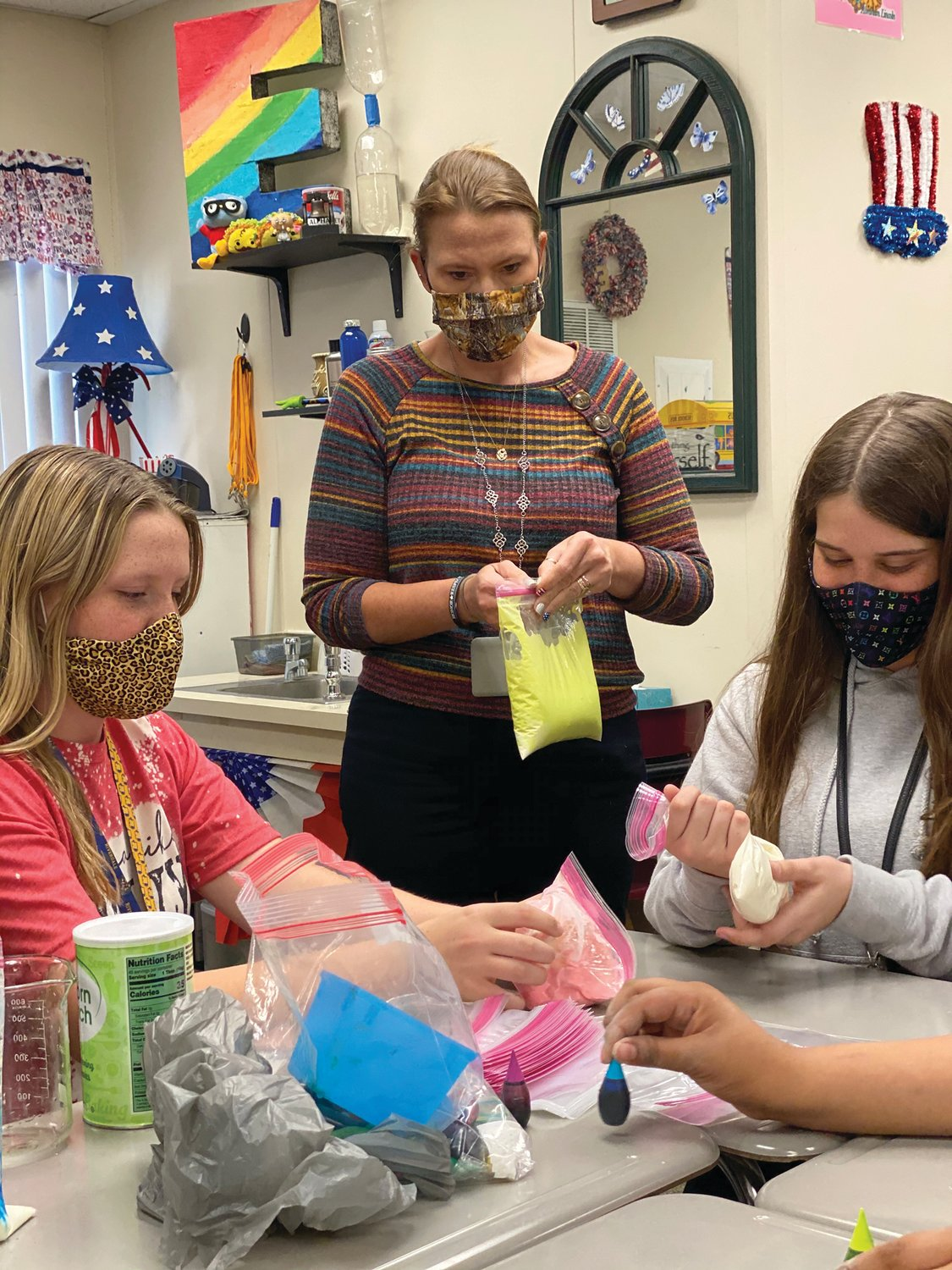 Kaydence Swanson, Mrs. Erskin, and Christy Woods make colorful, ballistic gravy for their epic LaBelle Middle School Science Club Thanksgiving-themed experiment.