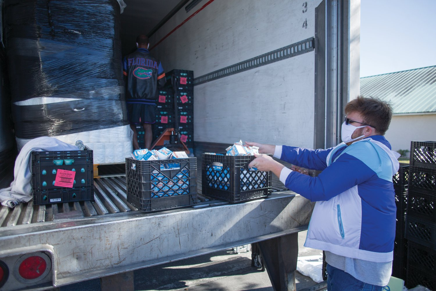 Volunteers help unload the tractor trailer full of food for needy families on Jan. 4.