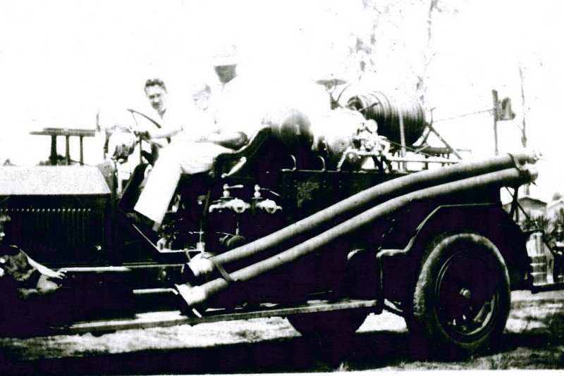 The boy in this picture is Bill Hendry, who grew up to become a county judge and local historian. This fire truck was used in the 1920s.