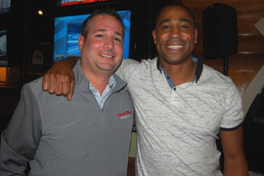 Vinny DiNatale (director of marketing for Grotto Pizza Inc.) with former Washington Redskin Fred Smoot.