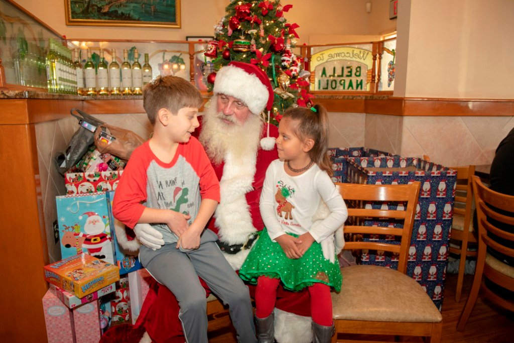 Santa with (l-r) Asher Burroughs (age 7) and Zaida Burroughs (age 5) of Glen Burnie.
