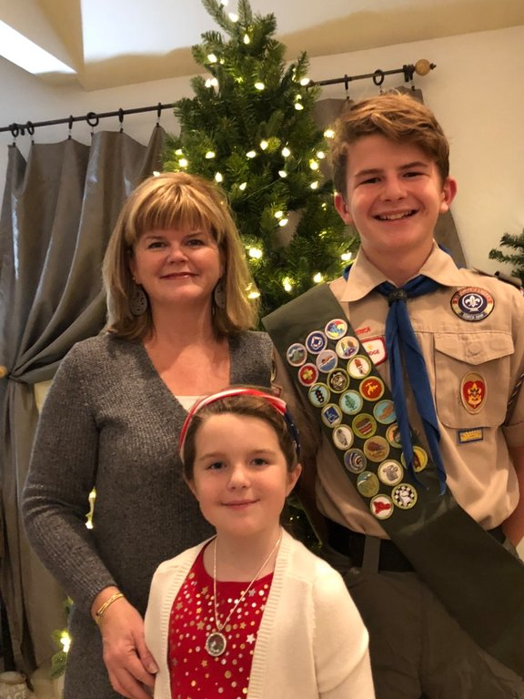 Fletcher Port (right) is trying to achieve the rank of Eagle Scout by building shelves at a USO warehouse and by sending care packages to members of the military. He is pictured with his mom, Amy, and sister, Zoe.