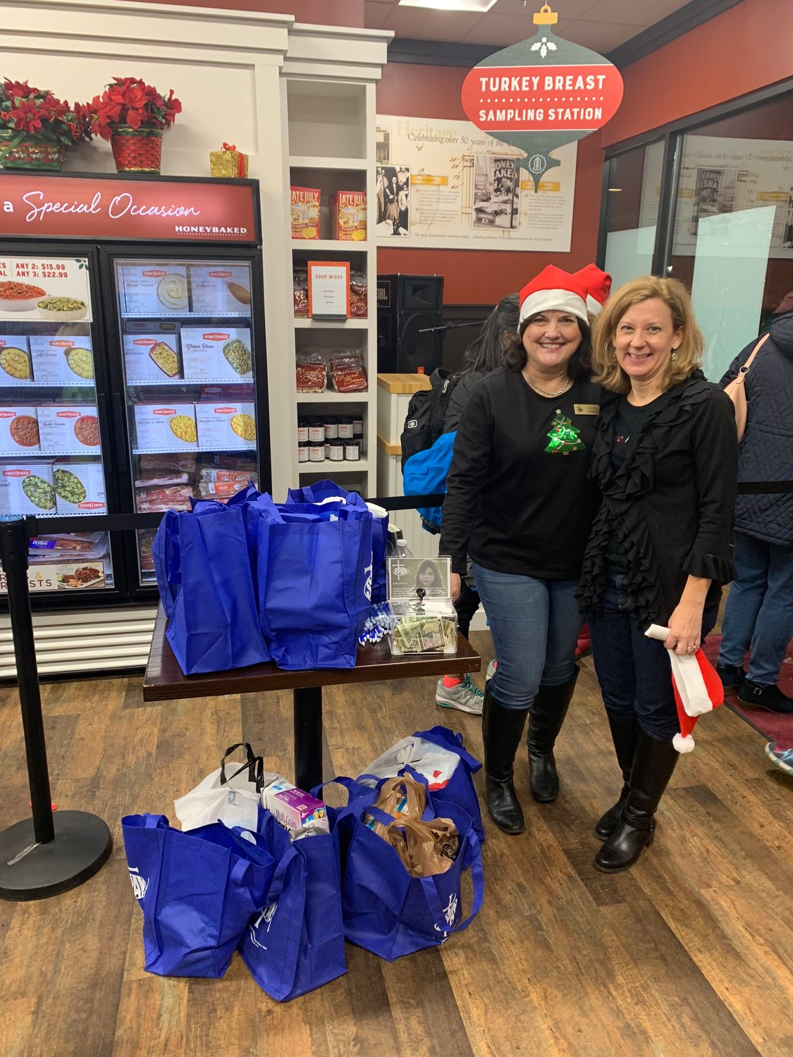 (L-R) Ellen Kinsella, director of development, and Jennifer Pumphrey, director of operations, collected 10 bags of nonperishable food and $51 for SPAN.