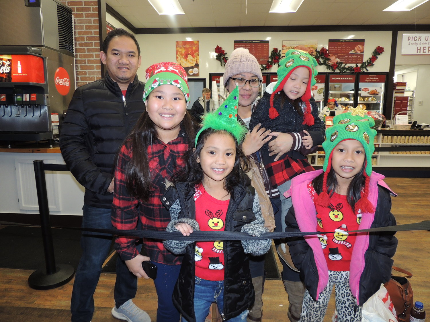 Children and parents eagerly gathered at Honey Baked Ham in Park Plaza to visit with Santa and Mrs. Claus.