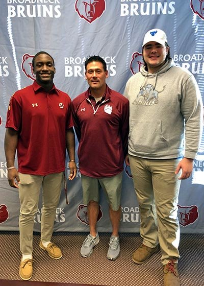 (L-R) Broadneck's Ethon Williams, coach Rob Harris and Caelan Shepard took part in a signing day ceremony on campus on Wednesday as Williams committed officially to play football at Boston College and Shepard committed to University at Buffalo.