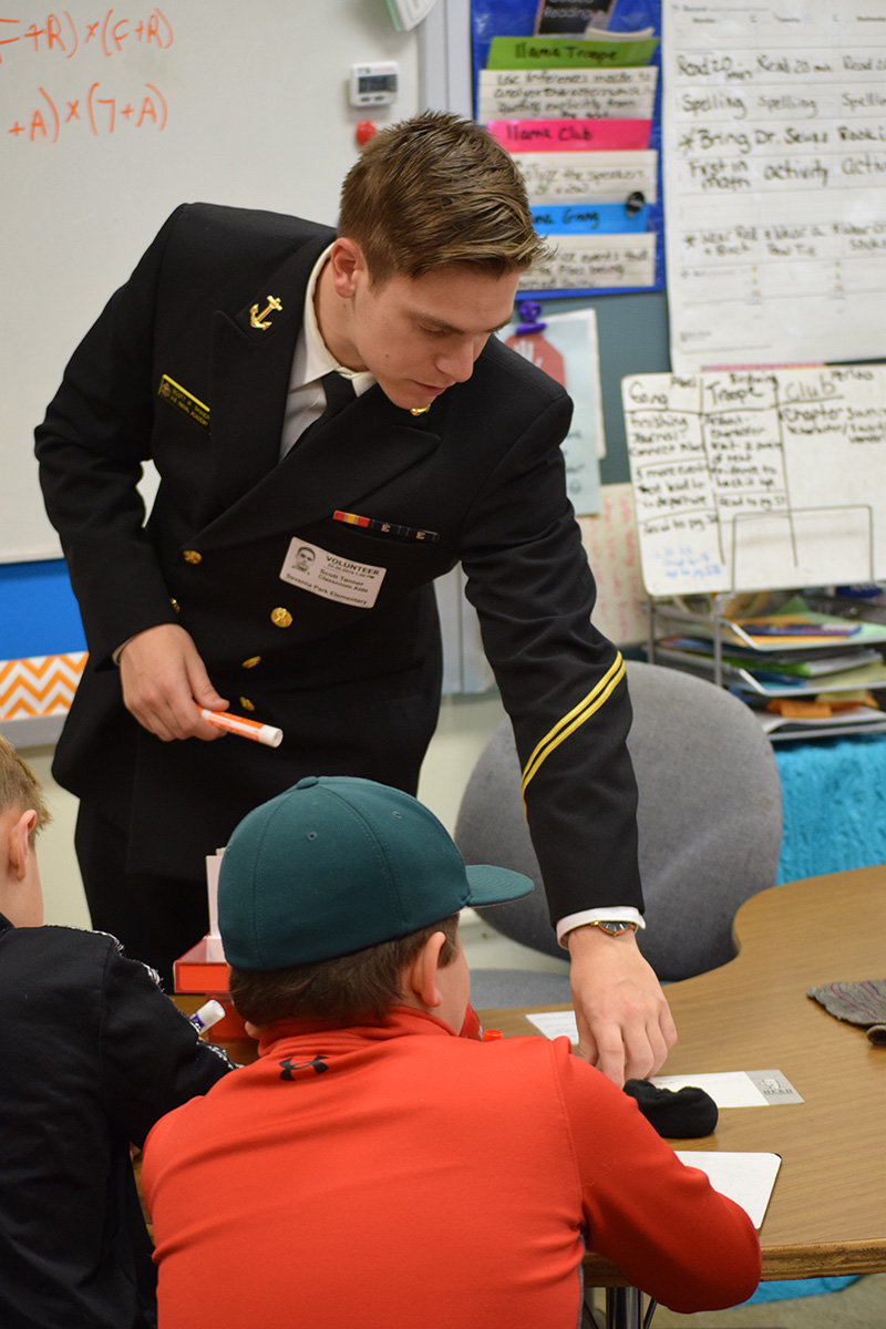 Midshipman Scott Tanner worked with a small group of students on a math lesson.