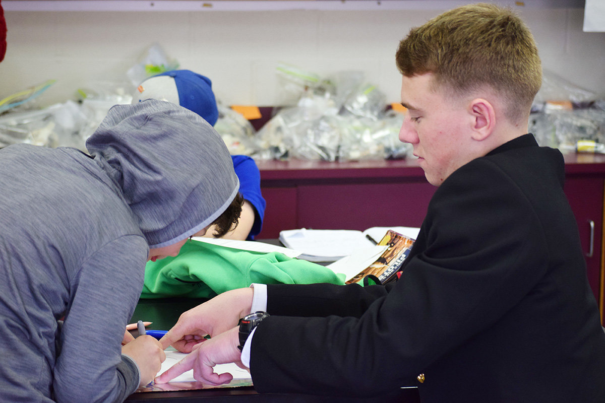 Midshipman Jack Bambury served as a helping hand while a student worked on a project.