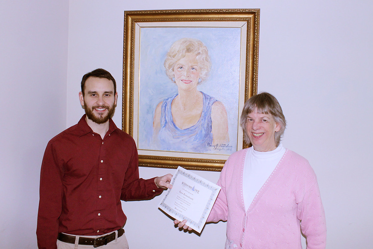 Severn River Association President Lynne Rockenbuach received her Volunteer of the Month award from Voice Assistant Editor Zach Sparks.