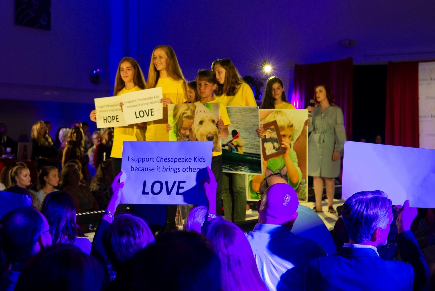 "Children present inspirational signs and photos while Annapolis Opera singer Patricia Hengen performs ""When You Walk through a Storm."" Children are from left to right, Chloe Chabot, Sage Christensen, Cole Christensen, April Lee and Addyson Papuchis."