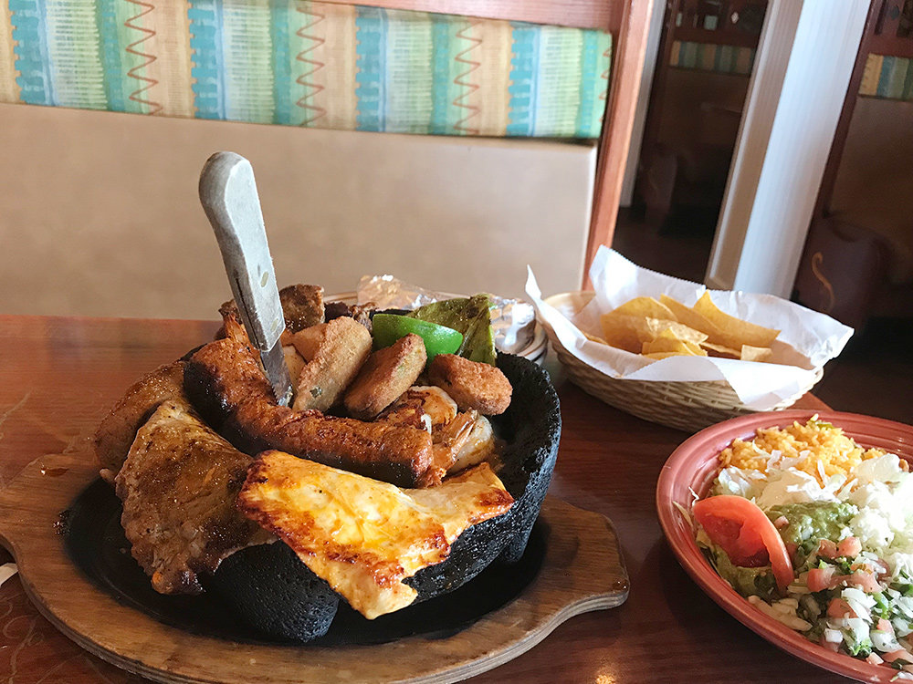 The El Molcajete features grilled rib-eye steak, shrimp, chicken and Mexican sausage, with cactus and jalapeno poppers on top of melted cheese and chipotle sauce, all served with a side of rice, beans, lettuce and guacamole.