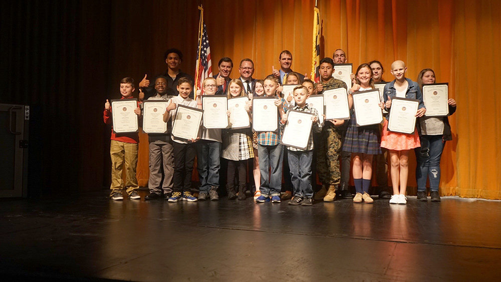 Winning essayists were invited onstage for accolades and photos with the legislators.