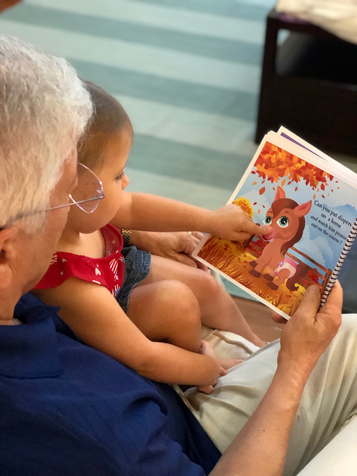 "Bill Sharkey read his book ""Can you Put Diapers on a Goose"" to his granddaughter, Reese."
