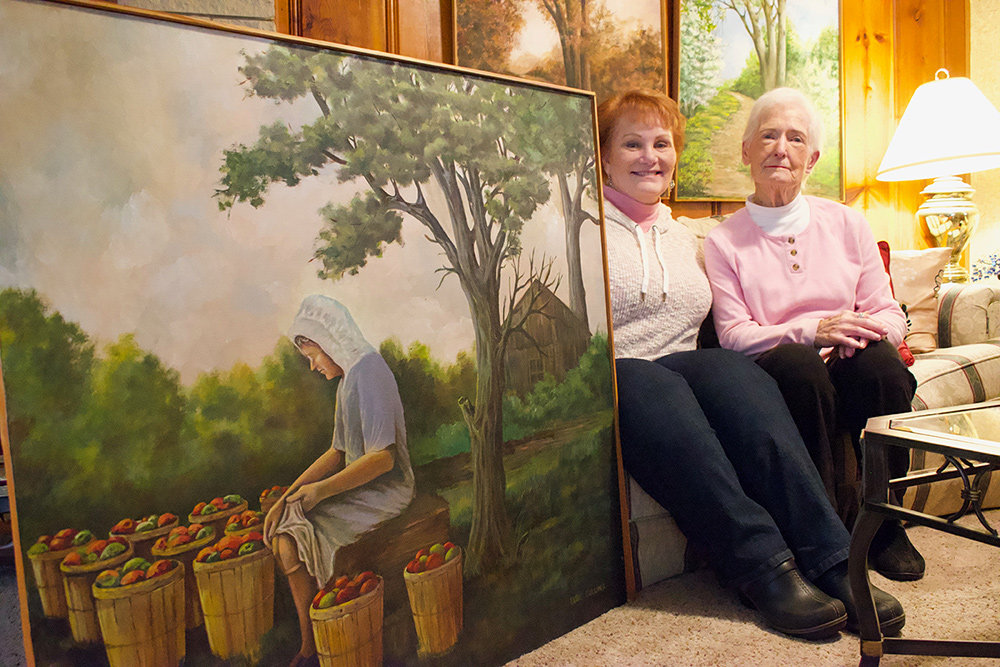 Celia Poteet and Elsie Cullins sat with Elsie's painting of her mother-in-law packing tomatoes. The Mountain Road Library is featuring works by both artists through February.