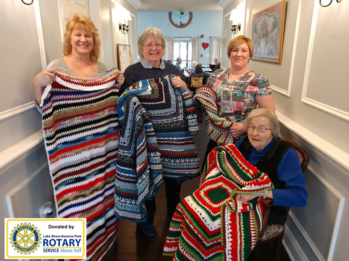 (L-R) Jennie Banner, PearTree House Assisted Living manager; Rotarian Bunnie Clark; Heather Hall, resident care manager; and resident Jeanne Beere (seated) all reflected on the afghan donation.