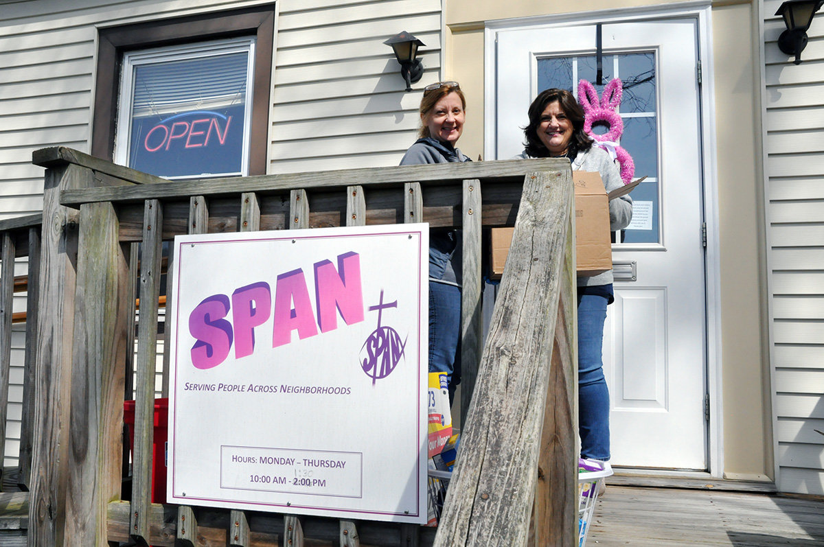 Ellen Kinsella (right), SPAN's director of development, and Jennifer Pumphrey, SPAN's director of operations, have asked people to show their identification through a window to get food SPAN left on its porch behind Our Shepherd Lutheran Church.