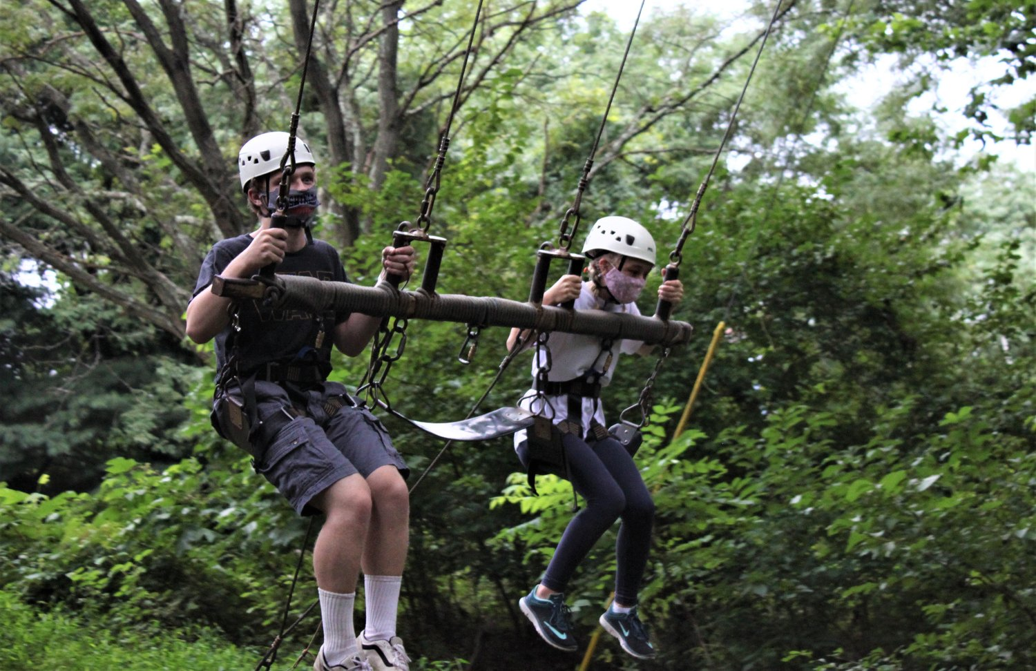 From left, Jeremiah Faust and Lillian Cross rode in a swing that flew high into the tree canopy during Camp Phoenix Teen Grief Camp held at Terrapin Adventures in Savage, Maryland.