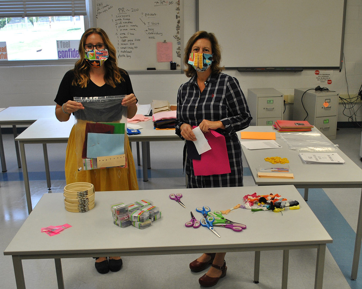 Rebecca Jenkins (left) and Angela Carbone put together sewing kits as part of the FACS e-learning curriculum.