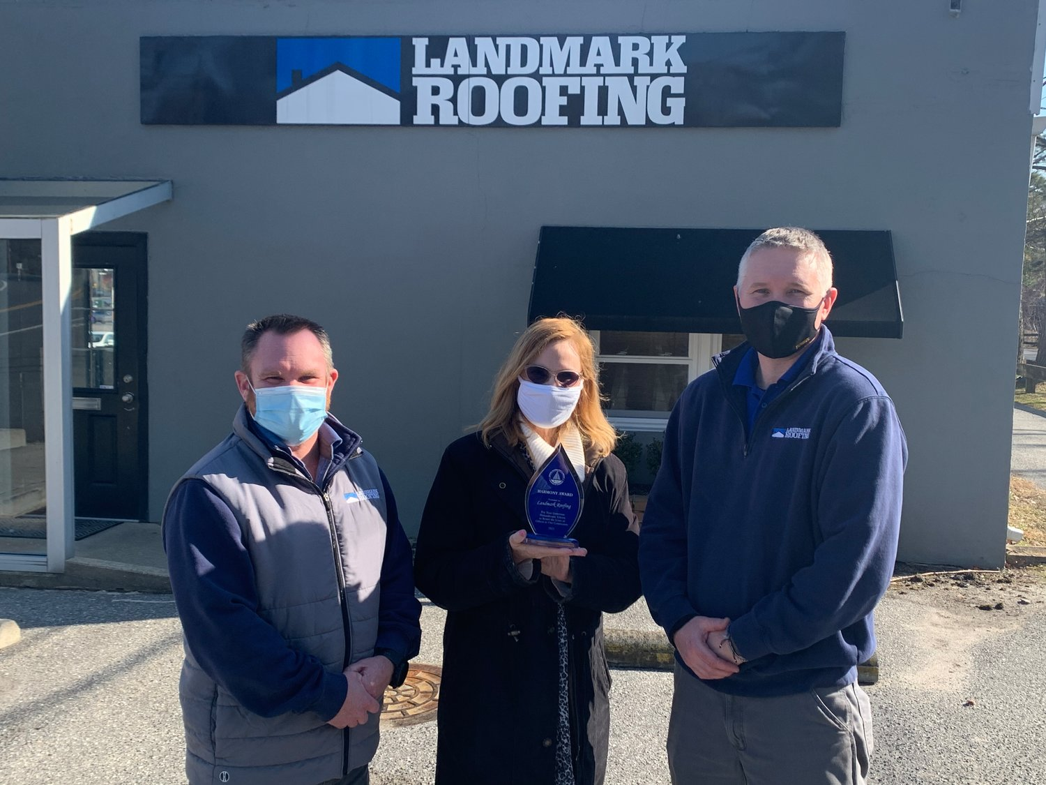 Greater Severna Park and Arnold Chamber of Commerce CEO Liz League presented Landmark Roofing owners Rob Calhan (left) and Artie Hendricks with this year's Harmony Award in recognition of giving back to the community.