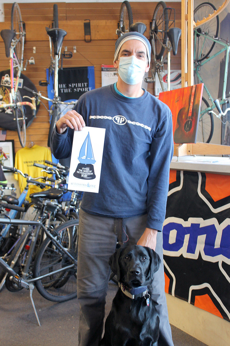 Pedal Pushers owner Rod Reddish and his dog were presented with a decal for Best Bicycle Shop.