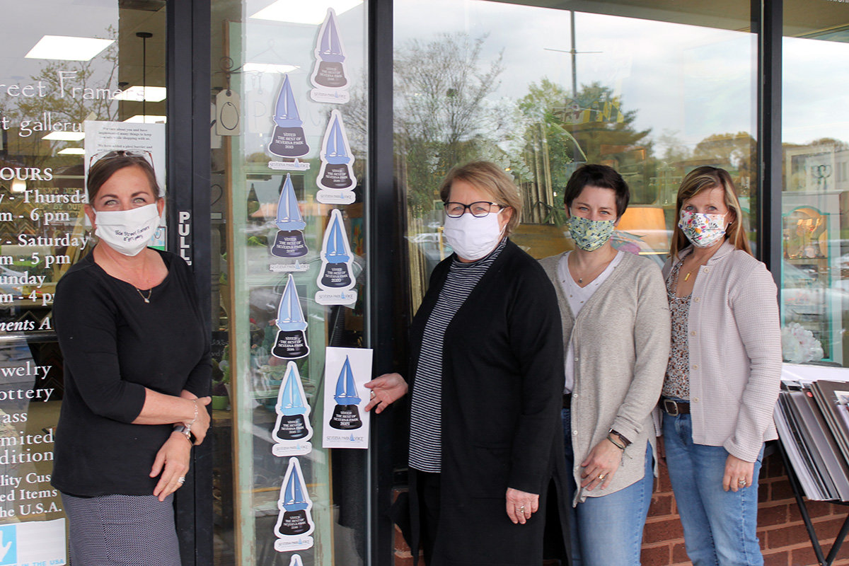 Side Street Framers staff members joined Barbara Daniels and Dawn Wilson to place this year's award decal.