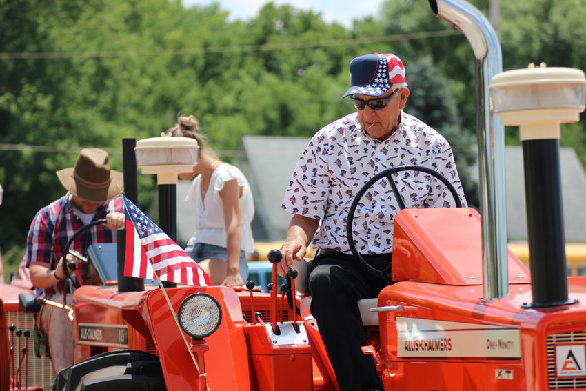 Duane Medow checks his gears and knobs before starting his tractor as the lead of the family's caravan on July 4 in Seward. He's driven in Seward's Fourth of July parade for years but never with all of his children and grandchildren on tractors.