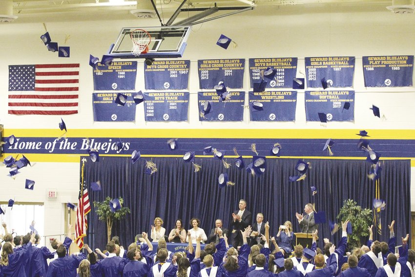 Seward High graduates toss their caps into the air as they celebrate the end of their high school careers on May 12. See more on page 16A.