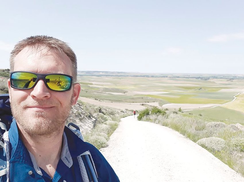 Tim Hartmann stops for a picture with the meseta in the background. Hartmann said this section of the Camino de Santiago in Spain was the most skipped by others, but he enjoyed how much it reminded him of Nebraska.