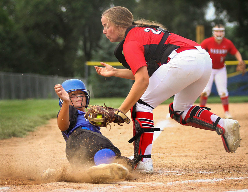 Malcolm's Taylor Glause is tagged out at home by Auburn catcher Shelby Neiman on a close play at home during Malcolm's 6-4 victory Aug. 22 in Malcolm.