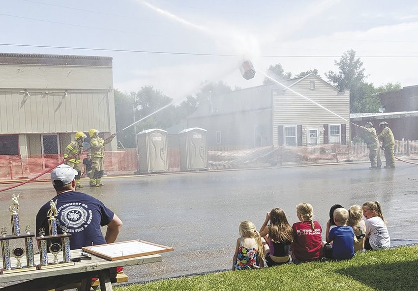 Spectators could feel the mist from the fire hoses June 22 as members of the Seward and Staplehurst volunteer fire departments battled for control of the barrel in the sky.Gresham and Goehner also participated in the water fight.