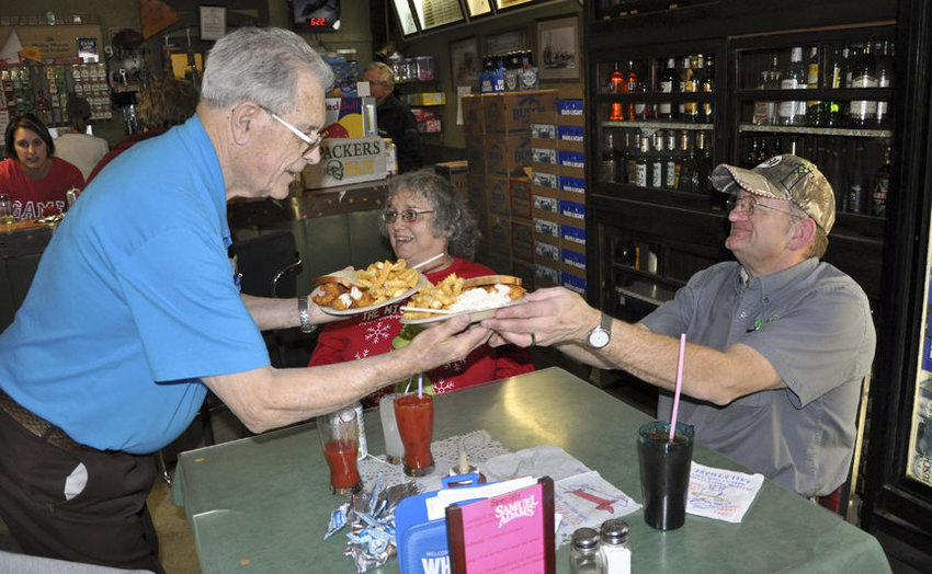 Lou Dart, owner of Lou and Mary Anne's Bar in Bee, serves fish to Bill and Kathy Payne of Seward Nov. 30 as part of the bar's long-standing Friday night fish fry tradition. The Paynes said the fish fry in Bee was their first date 15 years ago.