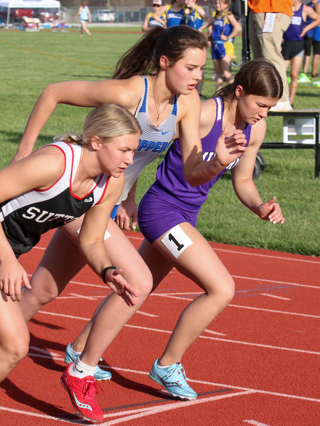 Jo Holliday of Malcolm (center) leaves the starting line in the 800-meter run at the Centennial Invitational April 26. She finished second in the race at the May 1 East Central Nebraska Conference meet.