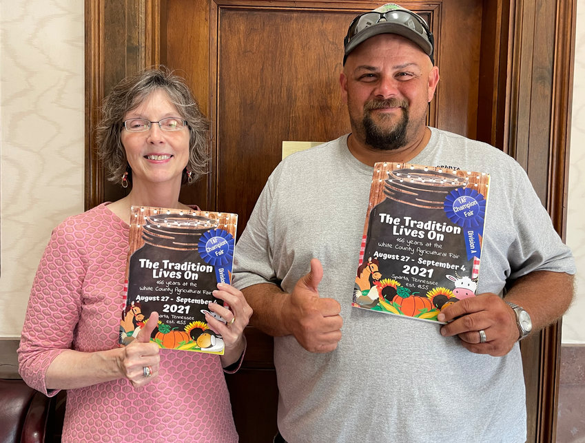 Paul Flatt, member of White County Fair Board, and Kim Swindell Wood, editor of The Expositor, give a thumbs-up to the newly designed 2021 fair book that is now available at the locations listed below.
