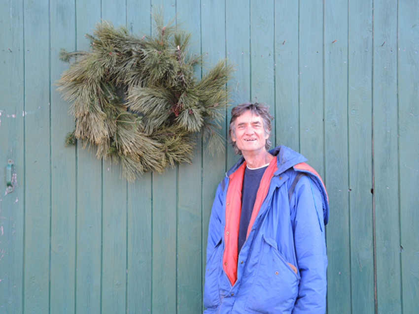 Mark Ramos, owner of The Fir Farm, stands in front of a wreath for sale at his farm.
