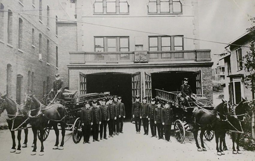 Photo provided by The History Center in Tompkins CountyMembers of Firehouse No. 9 stand in front of the brick firehouse with their equipment.