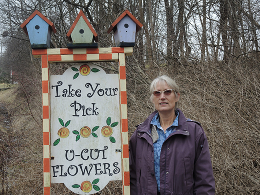 Photo by Sue Henninger.Linda VanApeldoorn at the entrance to her flower farm, Take your Pick Flower Farm in Lansing.