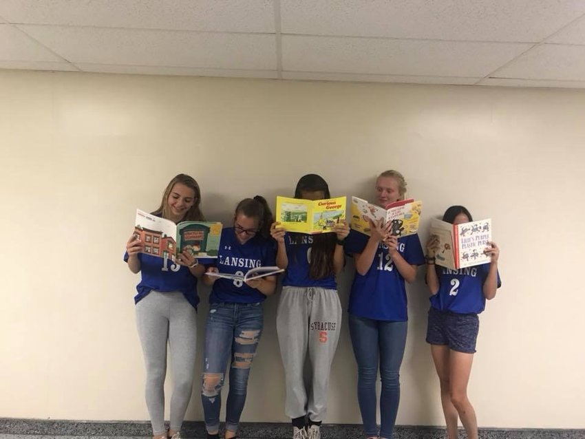 From left to right: Iris Boerman, Ashley Bell, Reace Todi, Gwen Gisler, and Corinna Petrich choose the books they would read to kindergarteners as part of a character building exercise.