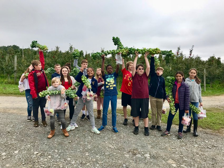 Seventh-grade students show off their brussel sprout harvest at Indian Creek Farm. The Project Based Learning model that Trumansburg schools utilize lets kids get hands-on education in a variety of areas.