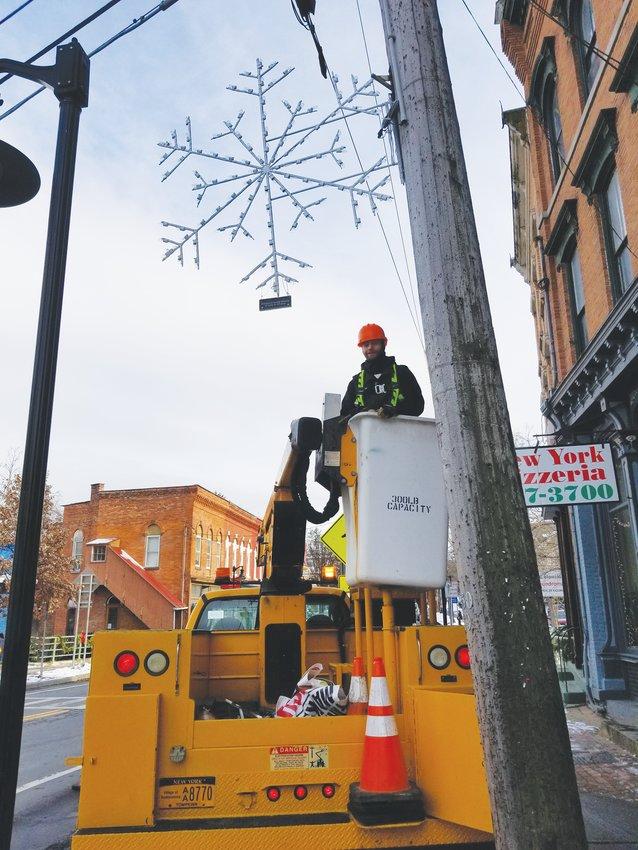 Dusty Vanderzee of the Trumansburg DPW installs one of the beautiful snowflake lights.