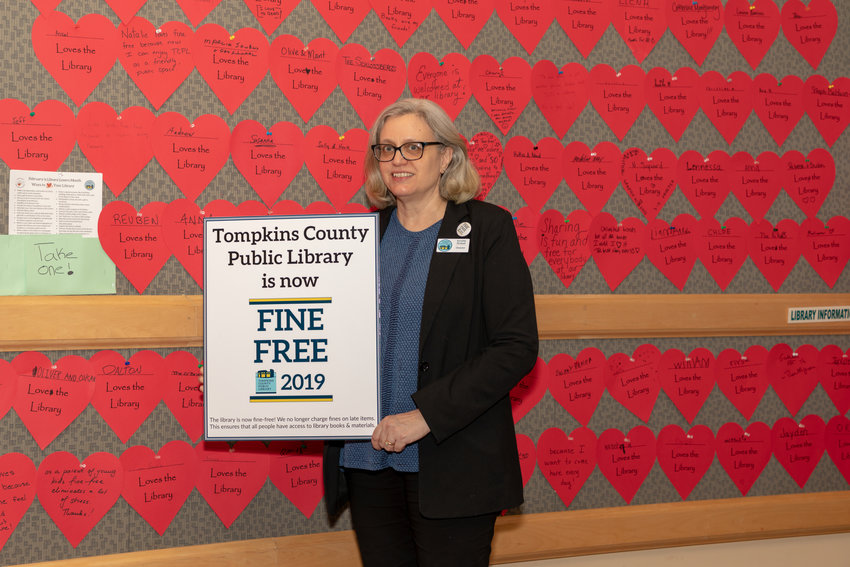 Tompkins County Public Library Director Annette Birdsall stands in front of the wall of hearts from patrons expressing their love of the library and the recent decision to go fine-free! Removing barriers like fines has been one of Birdsall's goals since before she was even named the TCPL Director.