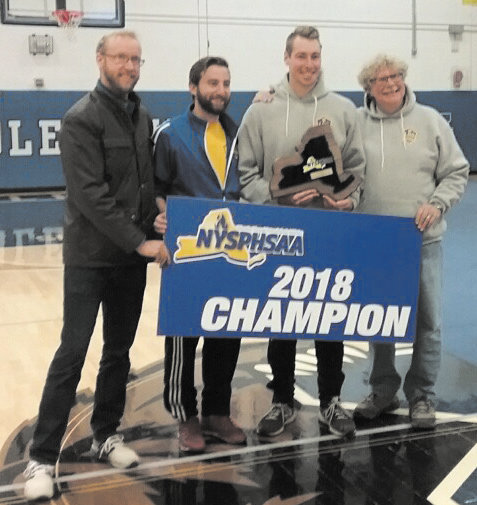 Streb, pictured left, stands with the rest of the Lansing Soccer staff in celebration of the 2018 state title. Streb will coach modified soccer in the fall and tennis this spring.