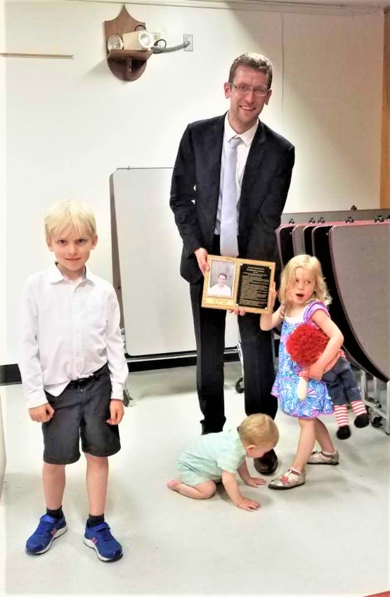 Groton High School Distinguished Graduate Hall of Fame, Dr. Sam Mackenzie, proudly displaying his plaque, along with his children, Henry and Alice, with baby Louis in the center.