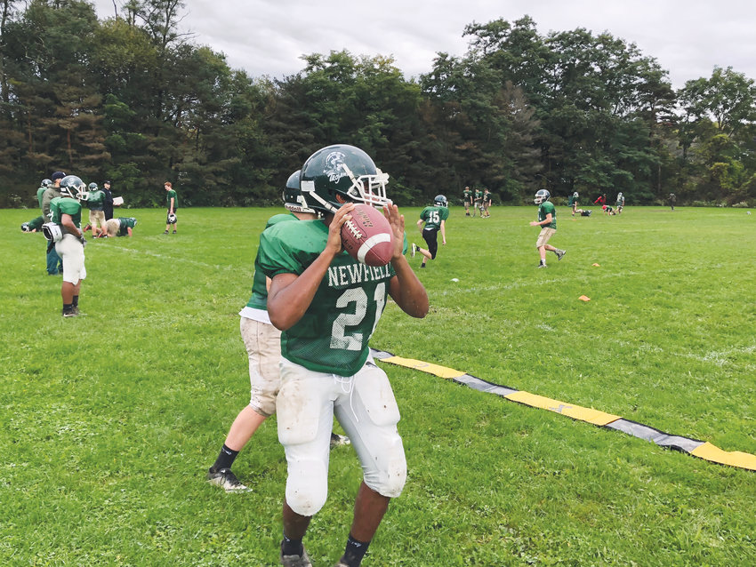 Arthur Hardison (21) returns to the Newfield Trojans at the quarterback position as the team practices, looking to overcome a two-win season in 2018.
