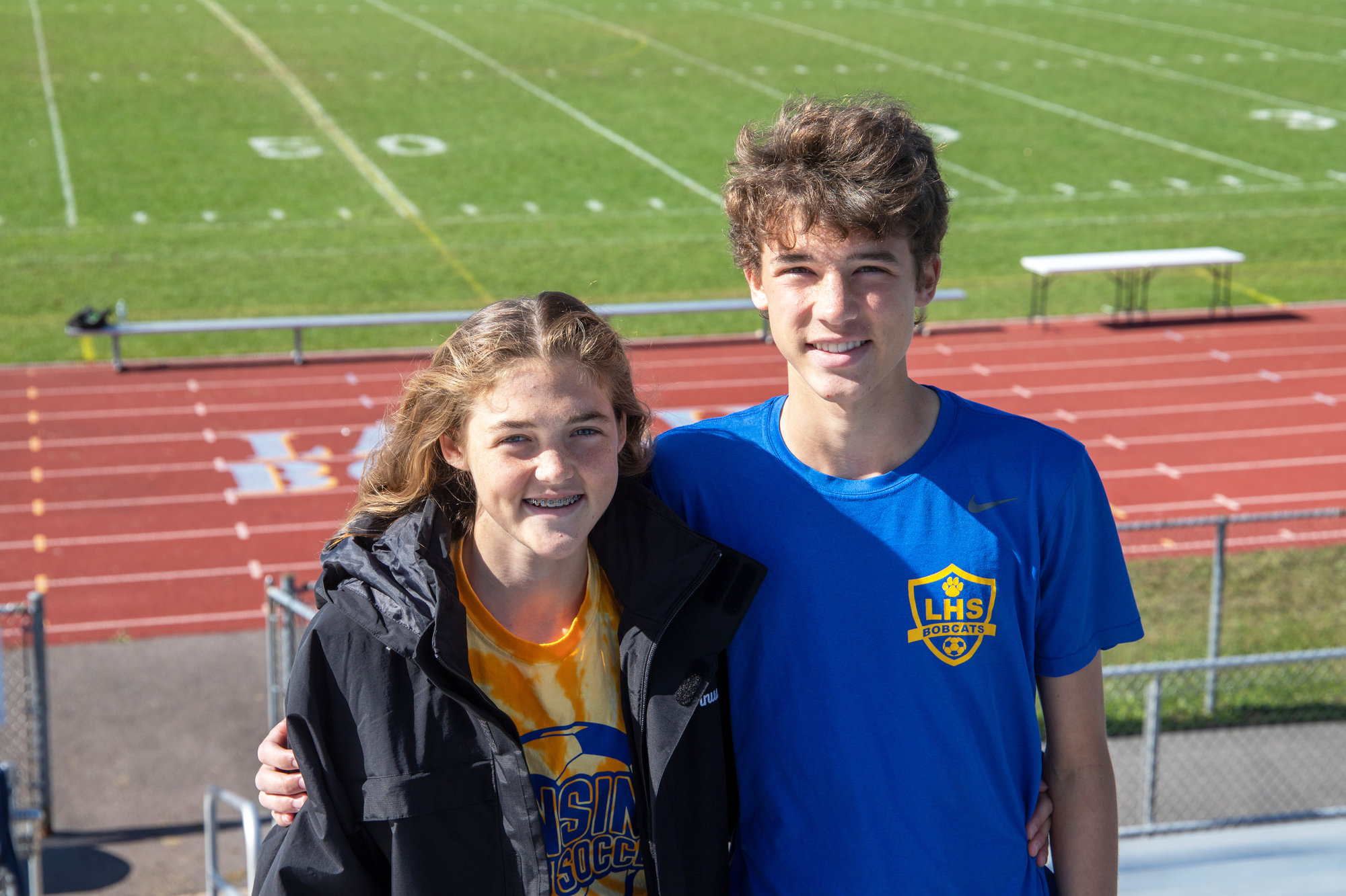 Kiara (left) and Julian Tornusciolo (right) stand in front of Lansing High School's Sobus Field. Kiara followed right in her brother's footsteps to join the Lansing soccer team.