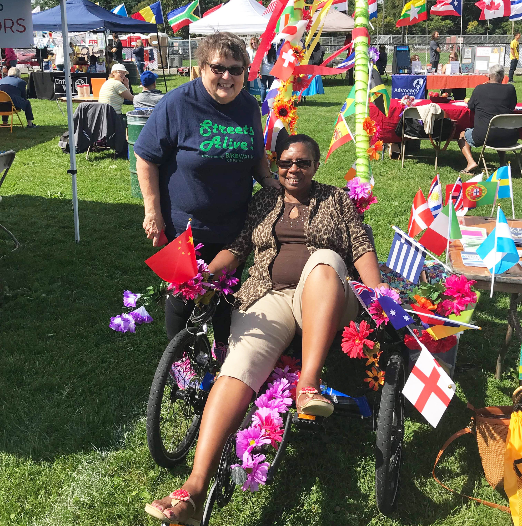 Barbara Kane-Lewis (left) with Muriel Trotman (right) at the 2019 GIAC Festival of Nations. The Bike Walk Tompkins booth theme was Bikes Around the World.