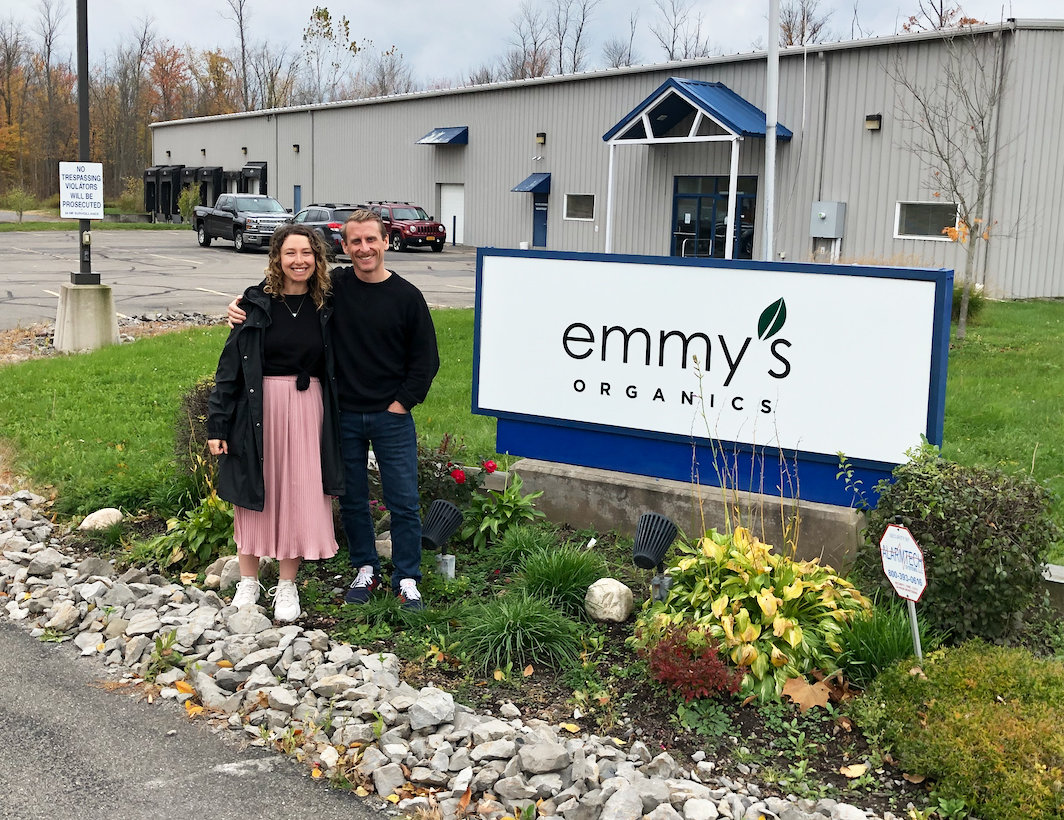 Samantha Abrams (left) and Ian Gaffney (right), creators of Emmy's Organics, stand in front of their new facility just off Hanshaw Road. The new location helps to bring all production under one roof, saving time and money for the food company.