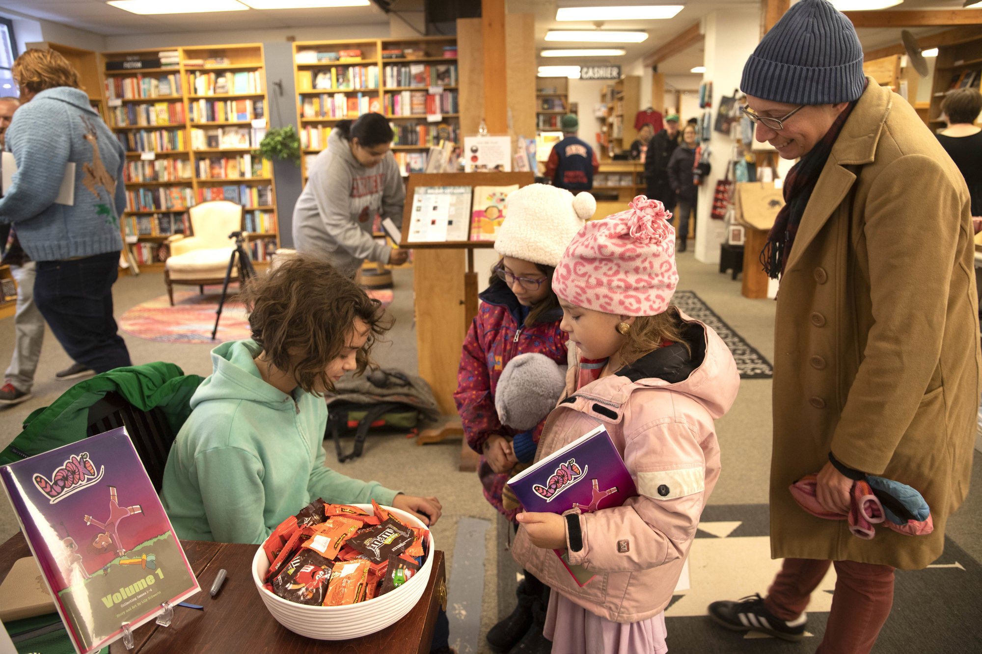 "Lily Schwartz (left), author of comic book ""Looki,"" signs a copy of her comic's first volume for Sophia (back) and Zoe (front) Tennant, accompanied by Jen Tennant (right), on Nov. 9's release at Buffalo Street Books."