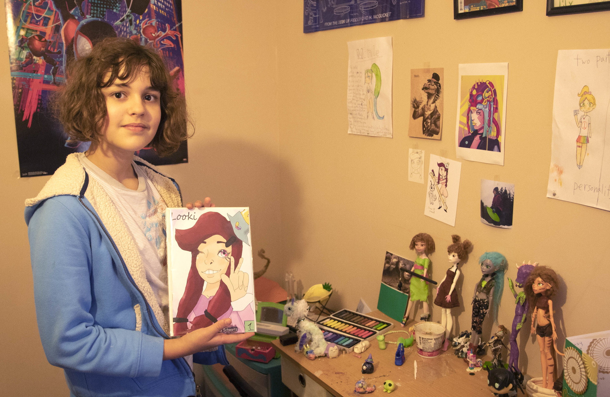 "Lily Schwartz, author of comic ""Looki,"" shows off her comic's first issue, which was released and printed for Ithacon 44 earlier this year. Her room shows off some of her other interests, like clay models and other forms of art."