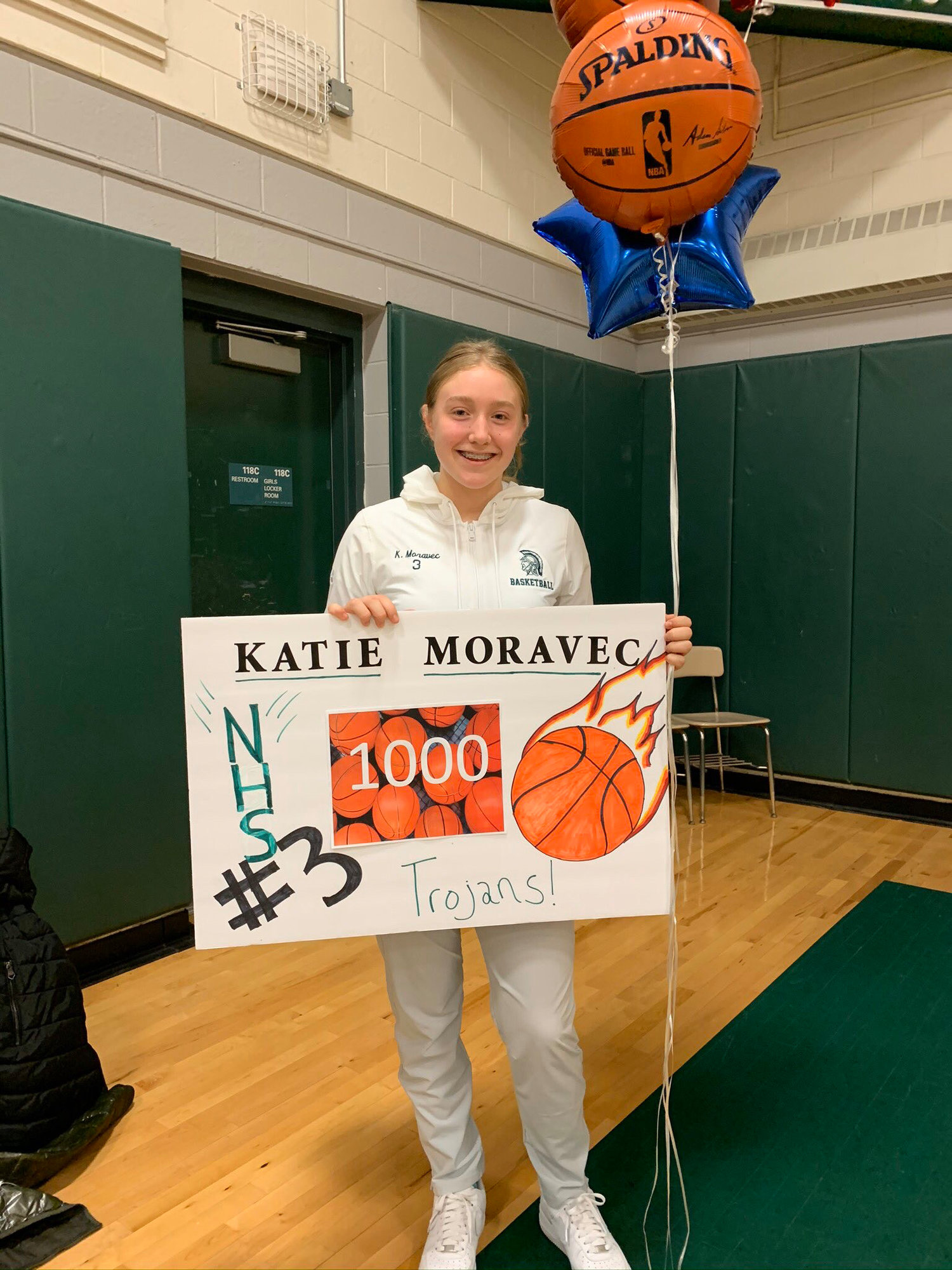 Junior Katie Moravec celebrates her 1,000 point milestone with a fan-made poster and balloons. Moravec has been a key member of the currently undefeated Newfield Trojans girls basketball team since eighth grade.