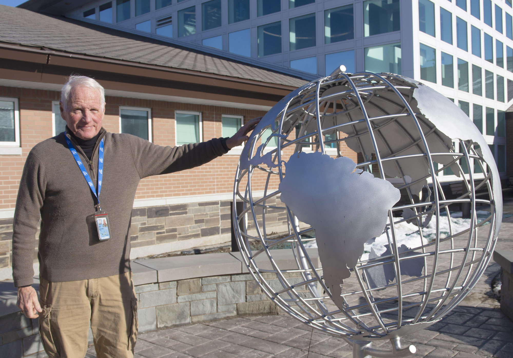 Ithaca-Tompkins International Airport Director Mike Hall stands next to a globe statue, built as part of the airport's expansion that recently completed in late 2019. The statue is meant to symbolize the airport's new global focus, Hall said.